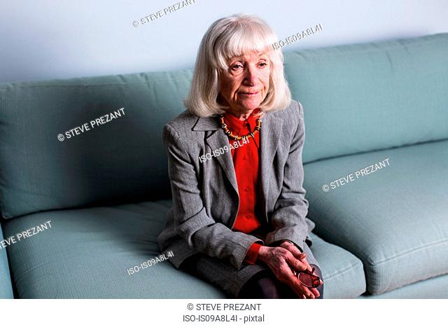 Senior woman sitting on sofa with blank expression