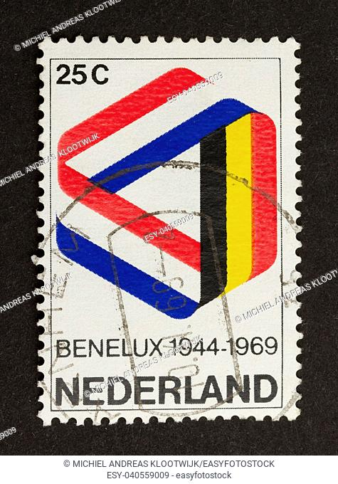 HOLLAND - CIRCA 1960: Stamp printed in the Netherlands shows the flags of Belgium, the Netherlands and Luxembourg, circa 1960