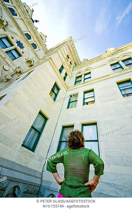 Young woman looking up at a building
