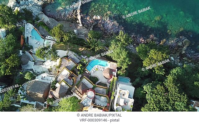 Aerial view of oceanfront villa in Mexico, zooming in on woman enjoying a bath in the swimming pool. Puerto Vallarta, Jalisco, Mexico