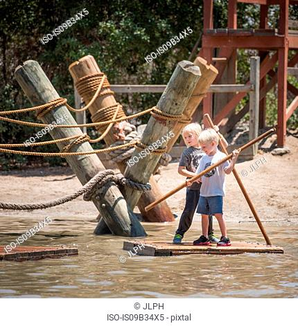 Boys holding sticks standing on raft