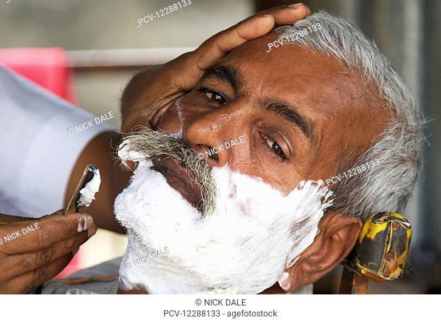 Face of Indian man being shaved; Dharpatha Mal, Madhya Pradesh, India