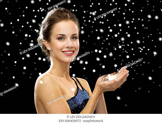 people, holidays and glamour concept - smiling woman with diamond over black snowy background