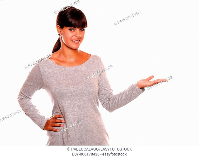 Portrait of a young woman holding out her left palm on grey dress and showing you copyspace standing over white background