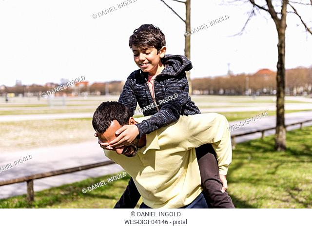 Happy father carrying son piggyback in a park