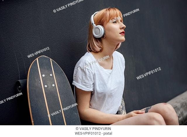 Young woman with skateboard and headphones listening to music