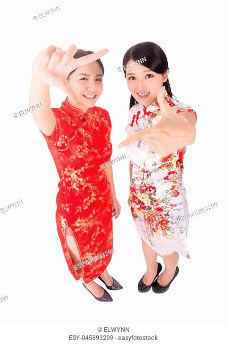Chinese woman in traditional cheongsam in the new year give you a gesture of frame