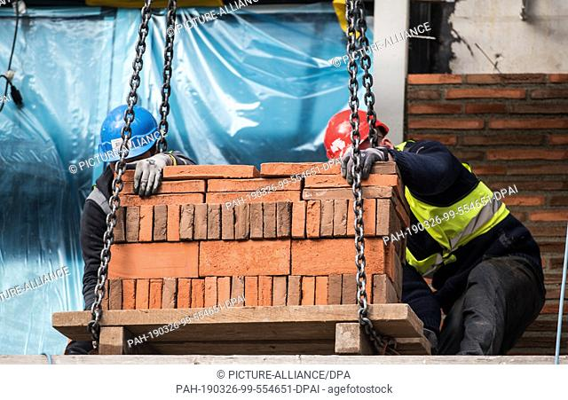 26 March 2019, Rhineland-Palatinate, Mainz: Construction workers set down a pallet of bricks. The façade is veneered with stones that are oriented towards...