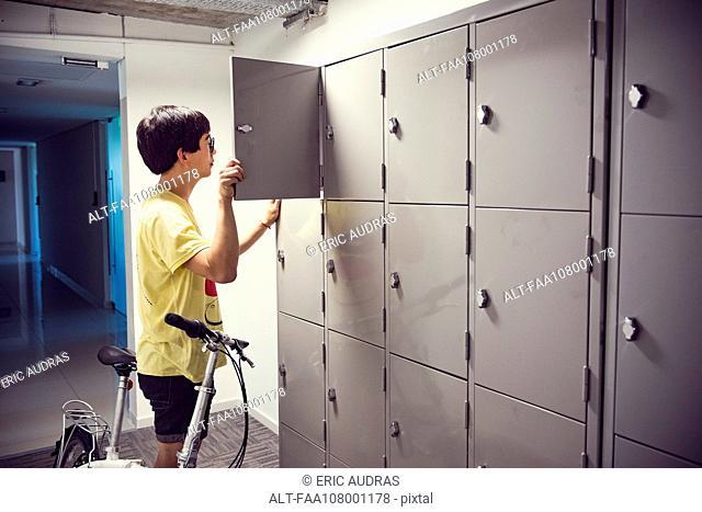 College student opening locker in corridor