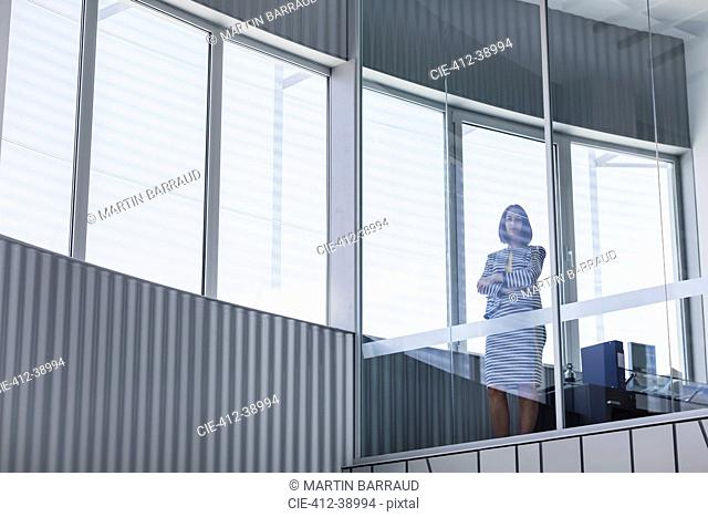 Portrait confident CEO businesswoman standing at modern office window