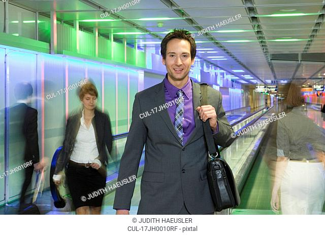businessman at airport, walking, happy