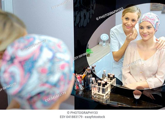 Beautician looking into mirror with client