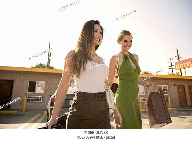 Young women outside motel, carrying suitcase