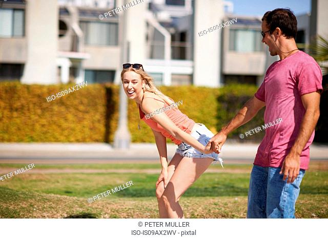 Couple fooling around outdoors, holding hands, laughing