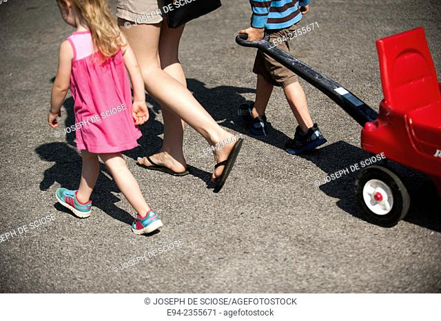 A partial view of a mother walking with her children and pulling a red wagon