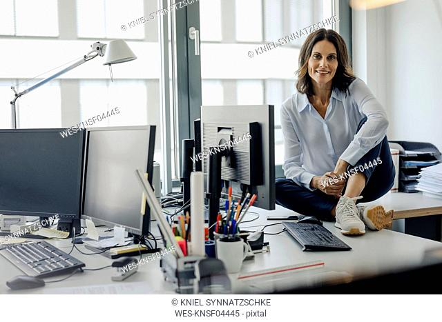 Mature businesswoman sitting o desk in office, smiling