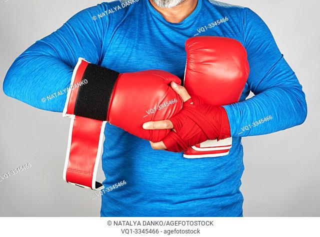 athlete in blue clothes, hands are rewound with red textile bandage, he is wearing leather sports boxing gloves, gray background