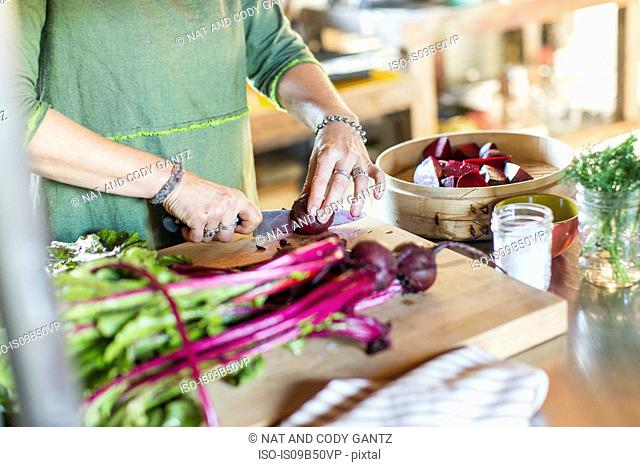 Mid section of woman slicing fresh beetroot on cutting board