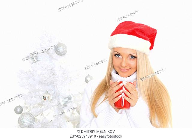 Young woman in Santa Claus cap with red cup stands near Christmas tree on a white background
