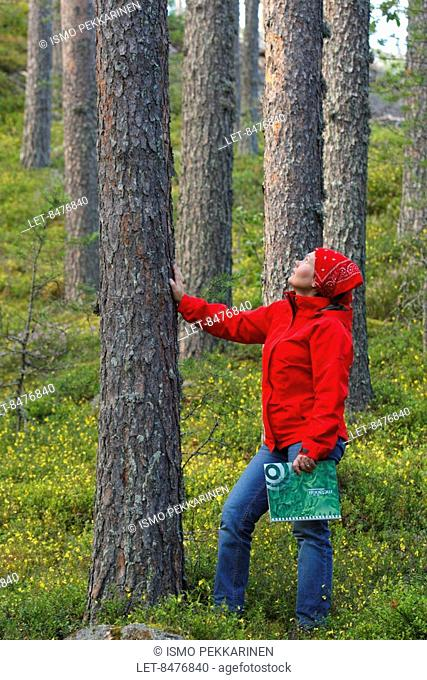 A forest owner observing her trees