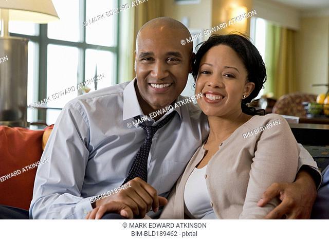 African couple hugging on sofa