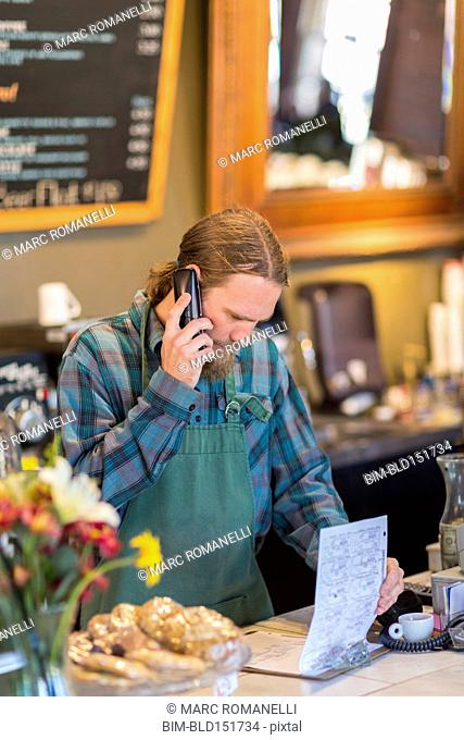 Caucasian server on telephone reading clipboard in cafe