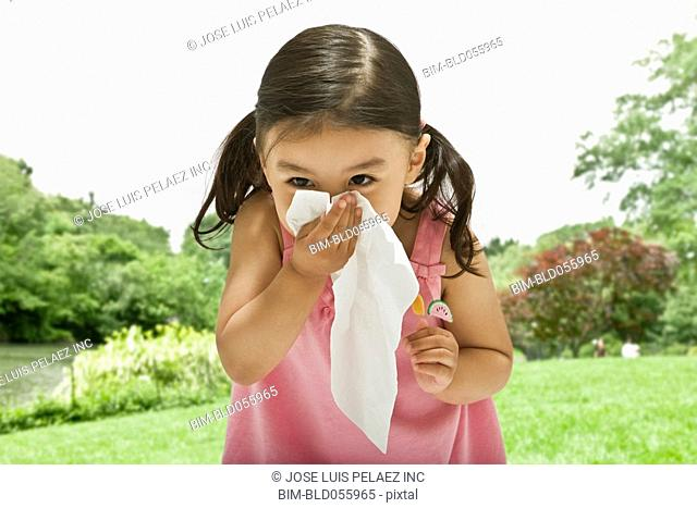 Asian girl blowing nose