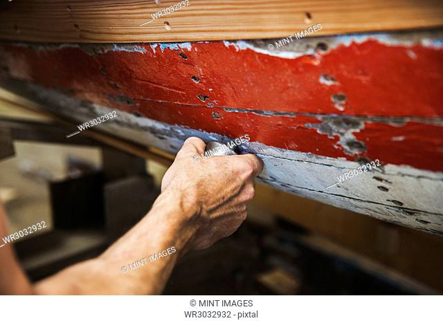 Close up of person in a boat-builder's workshop, working on a wooden boat hull