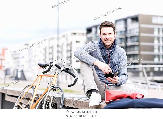 Businessman in the city with bicycle using smartphone and earphones