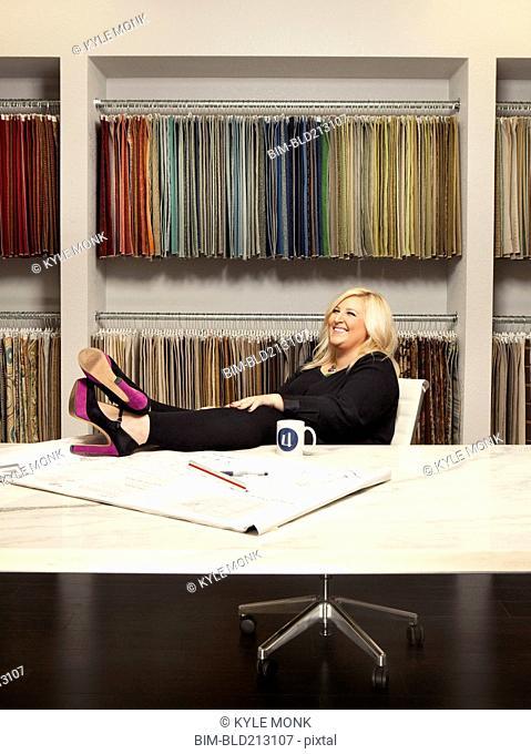 Caucasian interior designer sitting in studio