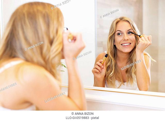 Lovely woman applying mascara in front of mirror. Debica, Poland