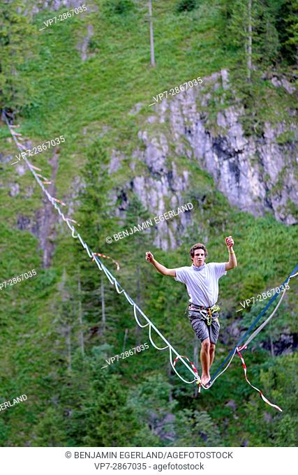 young man balancing on highline slackline over valley in nature, in south of Germany, Bavaria, near border to Austria