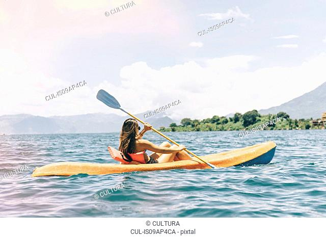 Young woman kayaking on Lake Atitlan, Guatemala