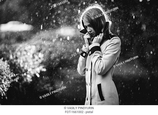 Thoughtful teenage girl wearing overcoat standing outdoors in rain