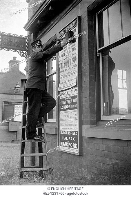 Billposting at Charwelton Station, Northamptonshire, 1904. A Great Central Railway employee sticking up a poster for the County Show outside the waiting room at...