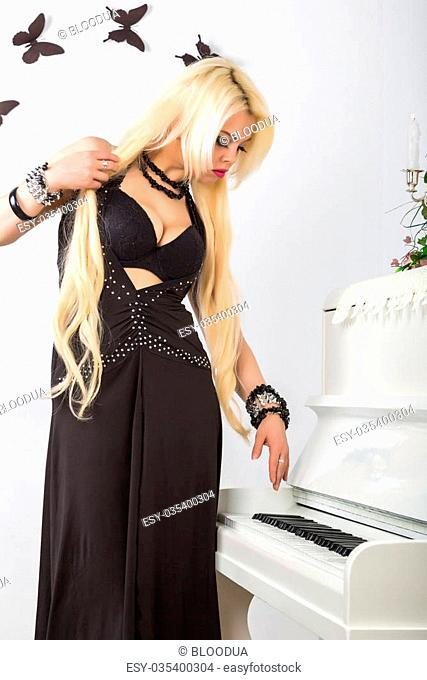 beautiful young attractive woman in evening dress and piano in a light room