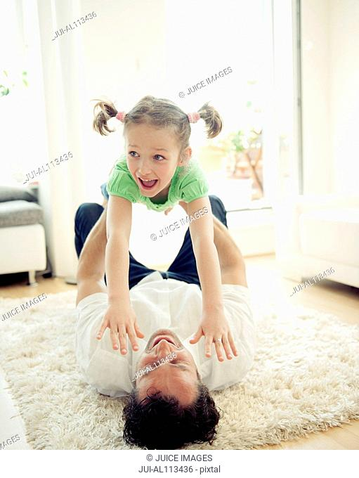 Father lying on floor holding up daughter