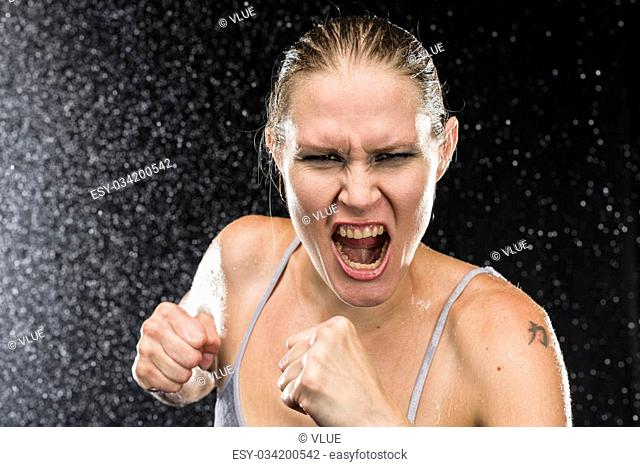 Close up Female Fighter Shouting Out Loud at the Camera with Angry Facial Expression Against Black Background with Water Drops Effect