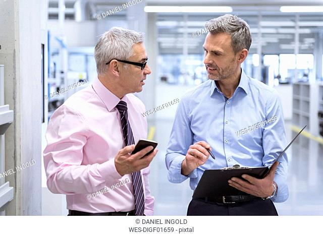 Two mangers discussing on shop floor of company