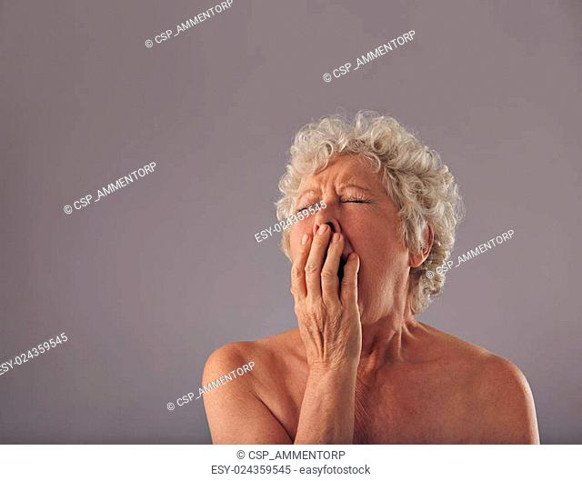 Naked senior woman feeling sleepy