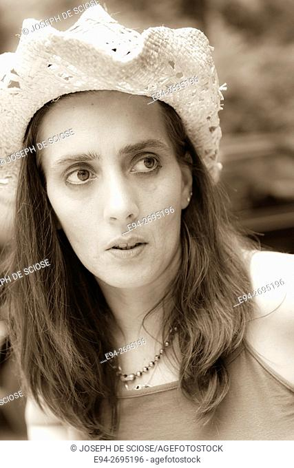 Portrait of a 42 year old brunette woman wearing a straw hat looking away from the camera, outdoors
