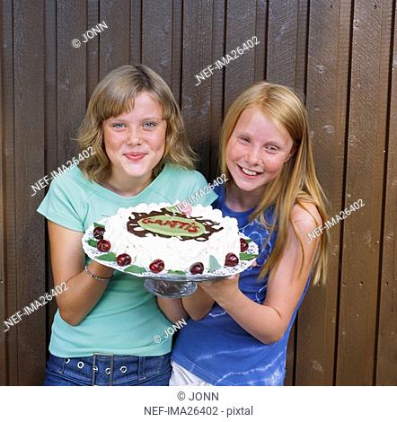 Pre teen girls holding birthday cake