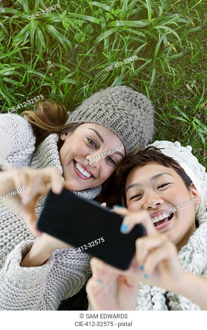Overhead view smiling women taking selfie with camera phone in grass