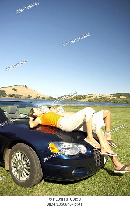 Couple relaxing on the hood of a convertible