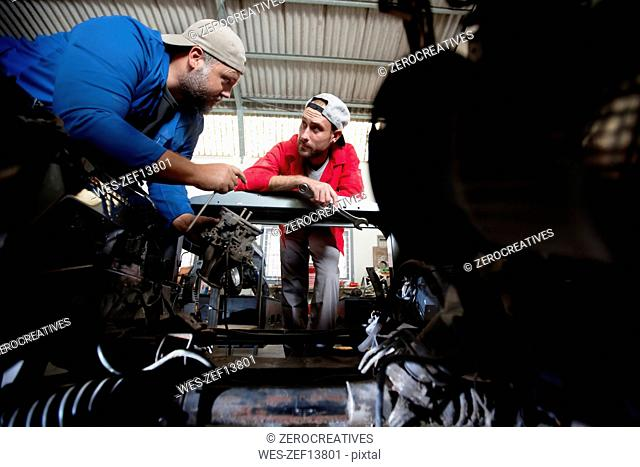 Mechanics repairing car in workshop