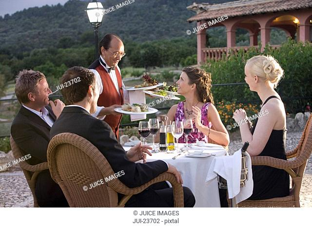 Waiter serving dinner to well-dressed couples at table on restaurant balcony
