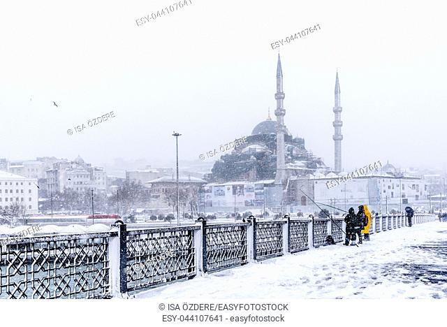 TURKEY, ISTANBUL, JANUARY 07, 2017: Unidentified men fishing at the galata bridge on the heaviest snowfall in Istanbul,Turkey