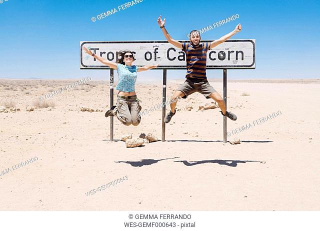 Namibia, Namib desert, Swakopmund, traveler couple jumping next to the sign of the Tropic of Capricorn