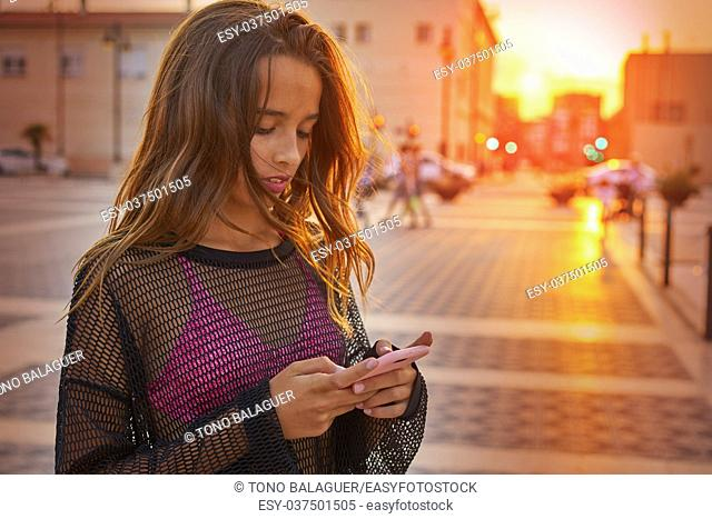 Teen girl texting chat on smartphone at sunset in the city