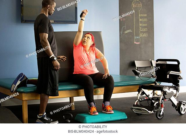 Disabled woman doing physical therapy with trainer